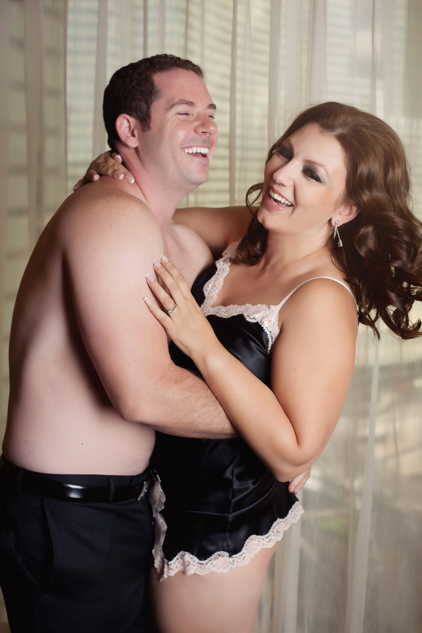 Couple having fun and laughing in their boudoir photography session in Las Vegas with Haute Shots.