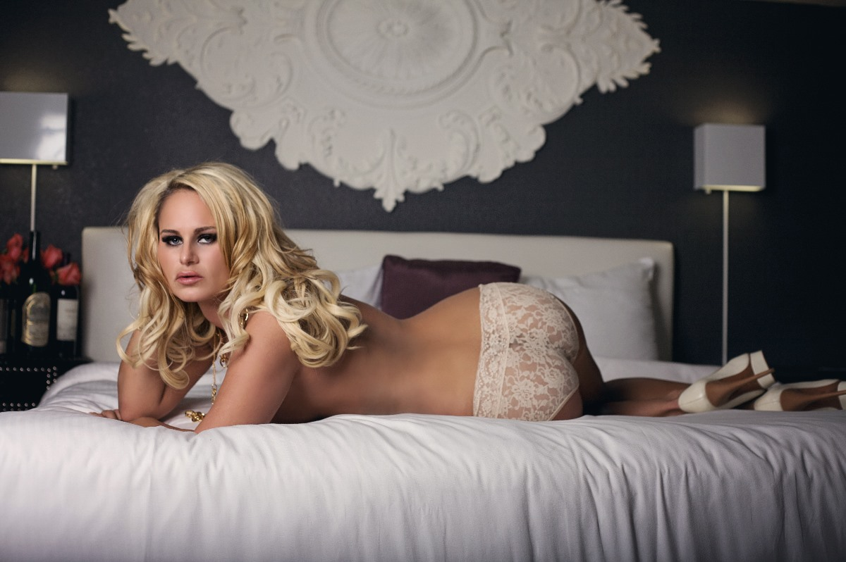 Pretty blonde posing on a bed for boudoir photos wit haute shots in las vegas.