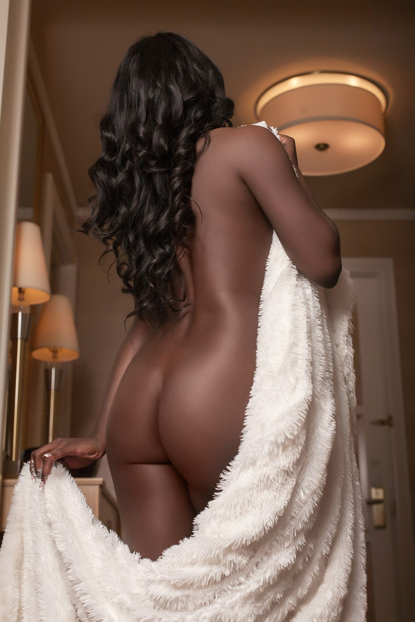 Boudoir client posing in hallway, implied nude. By Stacie Frazier of Haute Shots in Las Vegas.