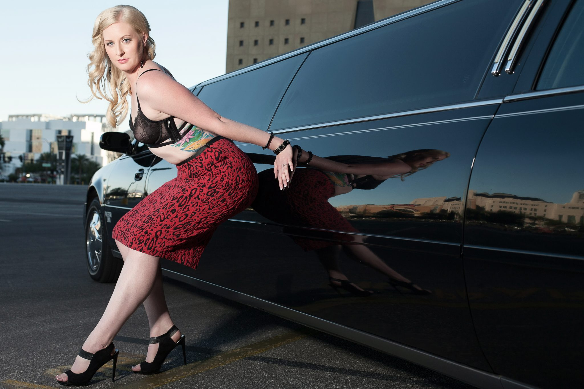 Posing in front of a limousine for boudoir photography shoot.