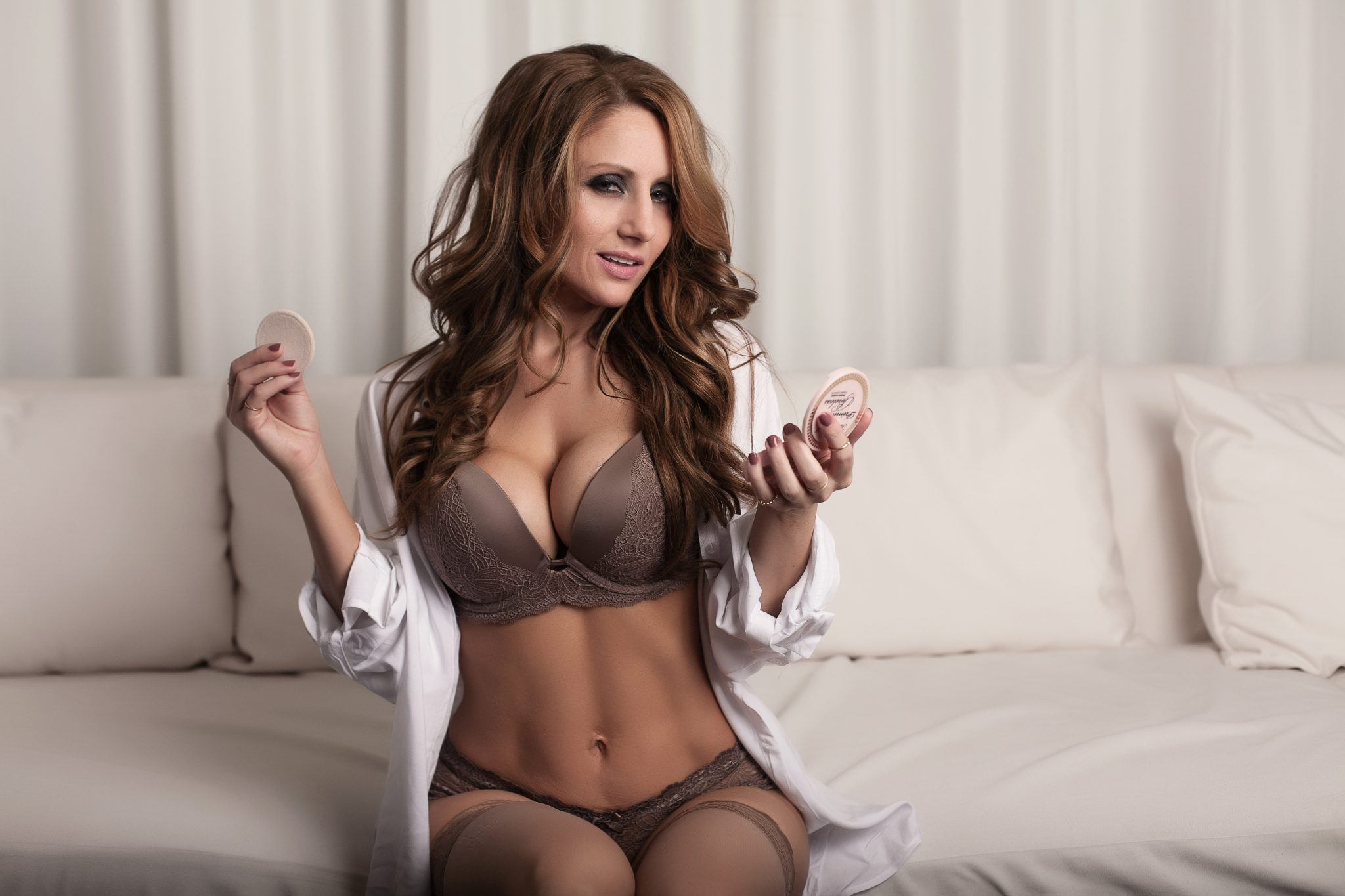 Powdering her nose in boudoir photos wearing bra and panty set with a man's white shirt.